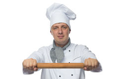 Chef in white holding a subject for rolling dough. Chef holding a rolling pin in his hand in front of a white Stock Photo
