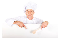 Chef in white uniform holding empty banner. Experienced chef in white uniform holding empty banner Stock Photo