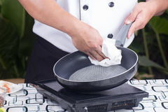 Chef wiping the pan before cooking Royalty Free Stock Photos