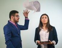 Chef wird die Papiere in einem MädchenBüroangestellten werfen, der schaut oben seine Augen verwirrte, die Tablette in den Händen  Stockfotos