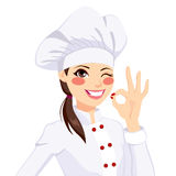 Chef Woman Gesturing Okay Sign. Young confident chef woman in uniform winking one eye and gesturing ok sign with her hand Royalty Free Stock Photos