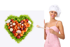 Chef woman pointing with a wooden spoon on the white billboard stock photo