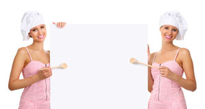 Chef woman pointing with a wooden spoon on the white billboard royalty free stock image