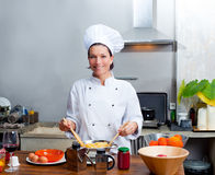 Chef woman portrait in the kitchen. Chef woman portrait with white uniform in the kitchen Stock Photography