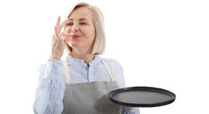 Chef woman showing sign for delicious. Female chef in uniform with perfect sign holding empty plate. Satisfied chef royalty free stock images