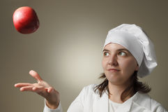 Chef woman throwing an apple Royalty Free Stock Photos