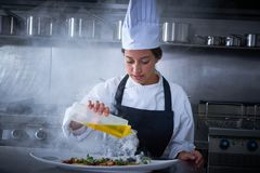 Chef woman working in kitchen with smoke Royalty Free Stock Image