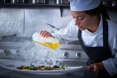 Chef woman working in kitchen with smoke Stock Photo