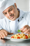 Chef at work. Happy smiling chef garnish an Italian pasta dish with basil leaves Stock Images