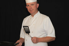 Chef at work. A male chef at work on a black background Royalty Free Stock Photo
