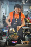 Chef at Work. A chef cooks food at a street-side restaurant on January 27, 2013 in Bangkok, Thailand. There are 16,000 registered street vendors in Bangkok Royalty Free Stock Photography