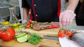 A chef working in the kitchen. Making a salad garnish to the steak. Mid shot stock video footage
