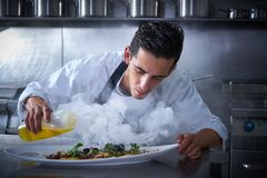 Chef working in kitchen with smoke and oil Royalty Free Stock Photos