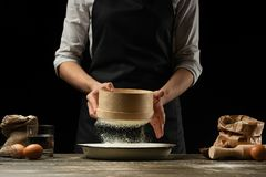The chef works with flour, for cooking focaccia, Italian pasta, pizza or bread. Freezing in motion. Concept of restaurant business stock images