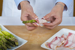 Chef wrapping asparagus with bacon slices Royalty Free Stock Photography
