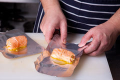 Chef wrapping up salmon rolls. In aluminum foil Stock Photos