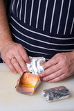 Chef wrapping up salmon rolls. In aluminum foil Royalty Free Stock Photography
