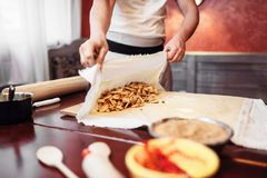 Chef wraps the filling into dough, apple strudel. Male chef wraps the filling into dough, apple strudel preparation process. Homemade sweet dessert Royalty Free Stock Photography