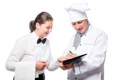 Chef writes something in a notebook on a white. Background Royalty Free Stock Photos