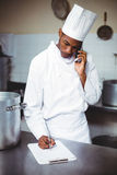 Chef writing on clipboard while talking on phone Royalty Free Stock Photography