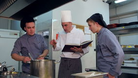Chef with young cook trainees in the kitchen preparing dish from the cookbook. Professional shot on Lumix GH4 in 4K resolution. You can use it e.g. in your stock video footage
