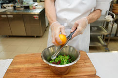 Chef is zesting orange in bowl with salad Royalty Free Stock Photos
