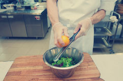 Chef is zesting orange in bowl with salad, toned Royalty Free Stock Images
