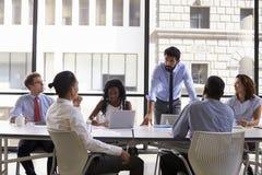 Chefanseende som tilltalar kollegor på ett affärsmöte arkivfoto