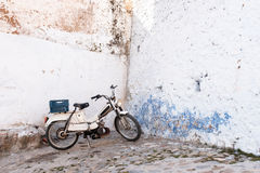 Chefchaouen medina, Morocco, Africa. Motorcycle parked on shabby empty street corner Royalty Free Stock Images