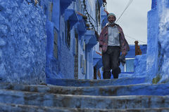 CHEFCHAOUEN, MOROCCO - FEBRUARY, 19 2017: Unidentified man walking in the blue medina of Chefchaouen Royalty Free Stock Images