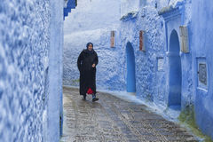 CHEFCHAOUEN, MOROCCO - FEBRUARY, 19 2017: Unidentified woman walking in the blue medina of Chefchaouen Royalty Free Stock Photos