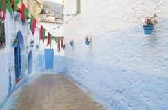 Chefchaouen-Straße mit marokkanischen Flaggen Stockfotografie