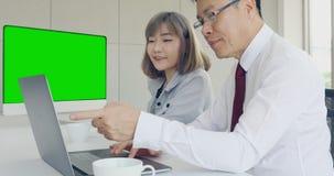 Chefe asiático e empregado que trabalham junto filme