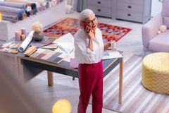 Chefe azul-enxaguado bem sucedido que fala no telefone ao guardar o copo de café imagem de stock