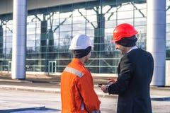 Chefe e trabalhador novos mim que discuto o projeto de construção na tabela foto de stock royalty free