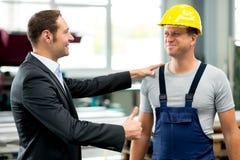 Chefe e trabalhador novos na fábrica imagem de stock