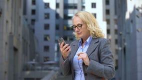 Chefe envelhecido da senhora que mostra o gesto do sucesso usando a aplicação do smartphone, mensageiro filme