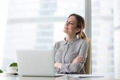 Chefe fêmea de sorriso que relaxa na cadeira do escritório com os olhos fechados fotografia de stock royalty free