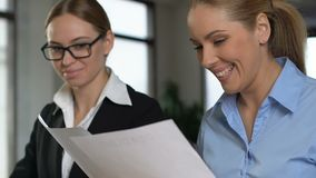 Chefe fêmea satisfeito que olha através dos documentos de trabalho, preparados pelo colega video estoque
