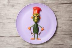 Chefe feito dos pepinos na placa roxa Fotografia de Stock Royalty Free