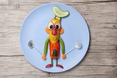 Chefe feito dos vegetais e das colheres na placa Imagens de Stock