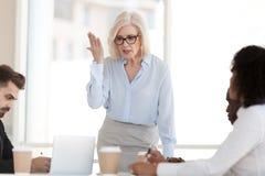 Chefe maduro poderoso irritado que discute empregados no grupo incorporado foto de stock royalty free