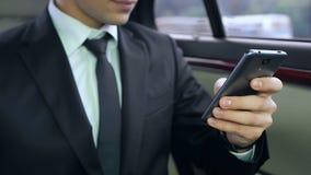 Chefe masculino novo que usa seu smartphone ao sentar-se no carro, reunião de negócios filme