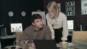 Chefe satisfeito da mulher que elogia o empregado para o bom trabalho no escritório escuro video estoque