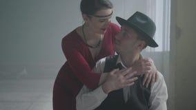 Chefe seguro considerável da máfia em um chapéu e em uma veste que sentam-se em uma construção abandonada A mulher elegante no ve video estoque