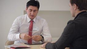 Chefen ger klienten ett affärskort stock video