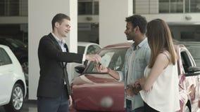 Chefen ger tangenterna från bilen till ett ungt par lager videofilmer