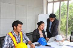 Chefen kontrollerar arbetet av teknikerlaget Planläggning av teknikerer och tekniker Tekniker- och arkitektplanläggning royaltyfri foto