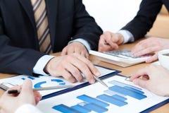 Chefer som arbetar sammanträde på tabellen Arkivfoto
