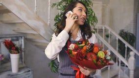 Cheffrauenfloristen-Anruftelefon zu ihren Kunden mit Blumen- und Frucht mischte Blumenstrauß stock video